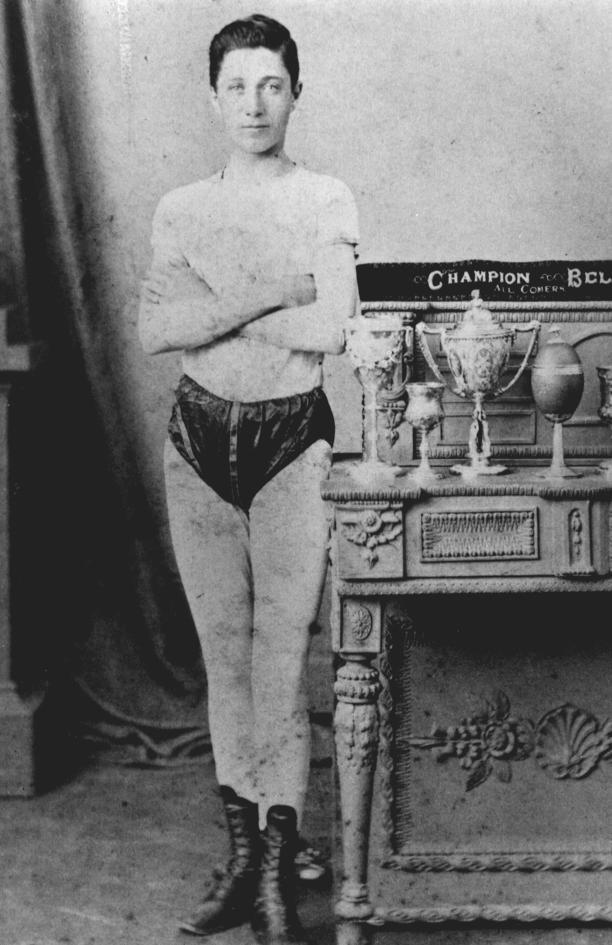 Joe Scott displaying trophies and belts